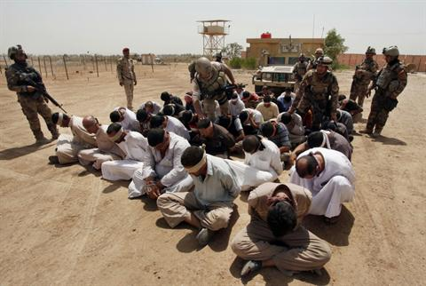 In this Friday, July 20, 2012 file photo, blindfolded and handcuffed suspected Al-Qaeda members are guarded by Iraqi army soldiers in an Iraqi army base in Hillah, Iraq.